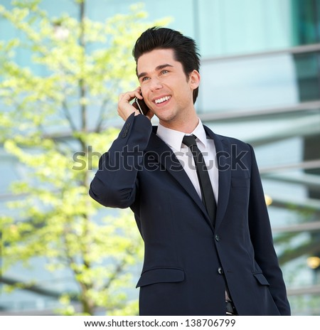 Close up portrait of a handsome businessman talking on mobile phone outdoors - stock photo