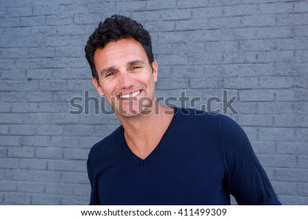 Close up portrait of a handsome guy smiling against gray wall - stock photo
