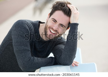 Close up portrait of a handsome man smiling with hand in hair - stock photo