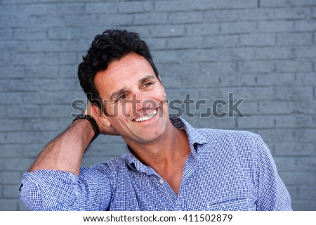 Close up portrait of a handsome man smiling with hand in hair against gray background - stock photo