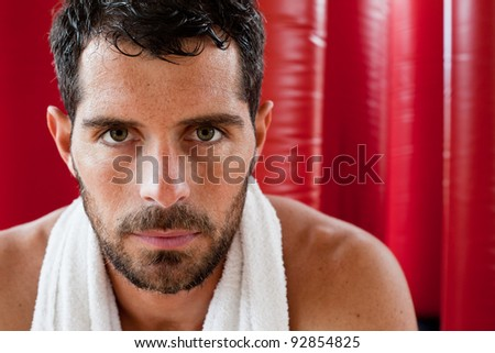 Close up portrait of a handsome muscular man with a towel on his shoulder sweating and looking tired staring at camera in front of red punching bags. Fighter. - stock photo