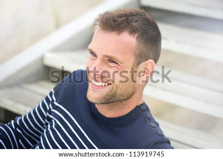 Close up portrait of a handsome smiling man sitting outdoors. - stock photo