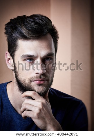 Close up portrait of a handsome thinking man with beard, blue eyes, hand under chin. - stock photo