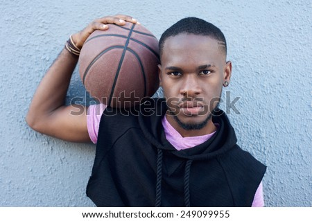 Close up portrait of a handsome young african american man holding basketball - stock photo