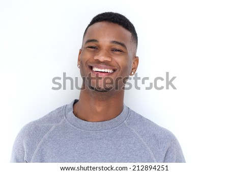 Close up portrait of a handsome young black man laughing on white background - stock photo
