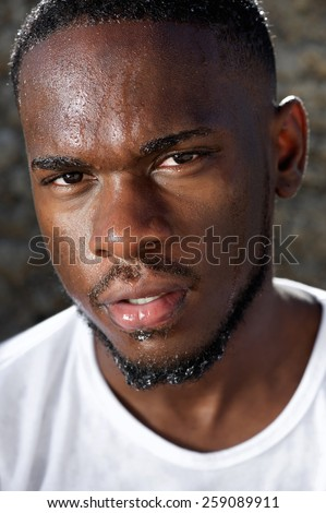 Close up portrait of a handsome young black man with sweat dripping down face - stock photo