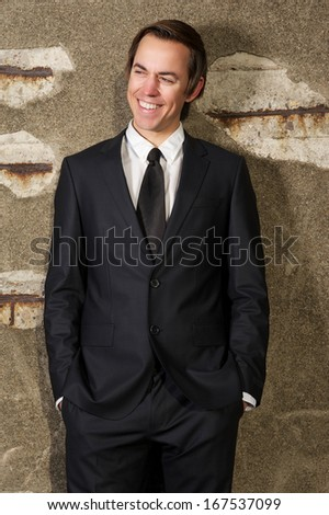 Close up portrait of a handsome young businessman smiling outdoors - stock photo