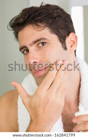 Close up portrait of a handsome young man applying moisturizer on his face - stock photo