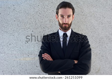 Close up portrait of a handsome young man in black business suit posing with arms crossed - stock photo