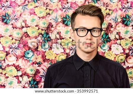 Close-up portrait of a handsome young man in spectacles over floral background. Men's beauty, fashion. - stock photo