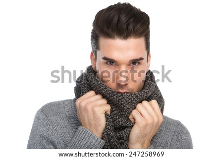 Close up portrait of a handsome young man posing with gray wool scarf on isolated white background
