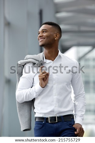 Close up portrait of a handsome young man smiling and walking  - stock photo