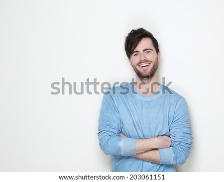 Close up portrait of a handsome young man smiling with arms crossed on white background