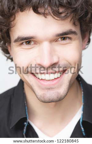 Close up portrait of a handsome young man with a smiling expression on his face. He is wearing a black shirt and is looking at camera - stock photo