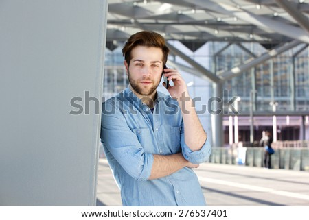 Close up portrait of a handsome young man with beard calling by mobile phone