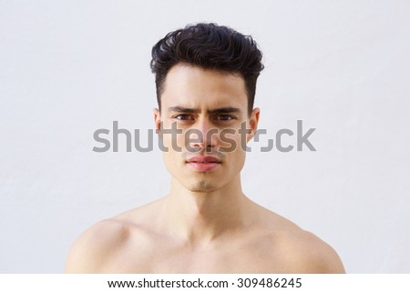 Close up portrait of a handsome young shirtless man posing against white background - stock photo