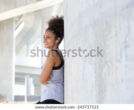 Close up portrait of a happy attractive young black woman listening to music with earphones - stock photo