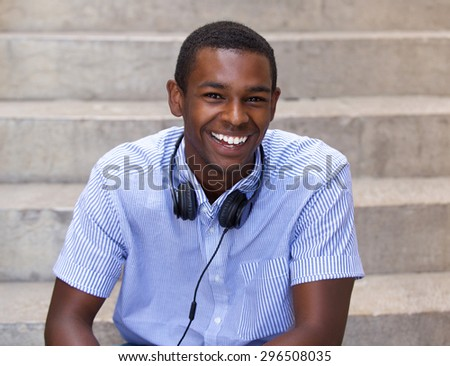 Close up portrait of a happy black guy sitting with headphones - stock photo