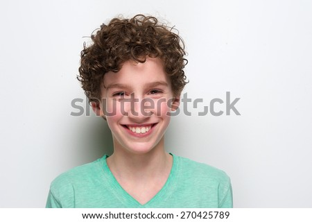 Close up portrait of a happy boy smiling against white background - stock photo
