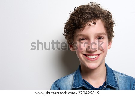 Close up portrait of a happy boy smiling on white background - stock photo