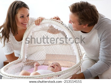 Close up portrait of a happy couple smiling with first child - stock photo