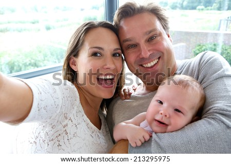 Close up portrait of a happy couple taking a selfie with baby - stock photo