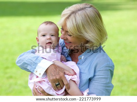 Close up portrait of a happy grandmother holding cute baby outdoors - stock photo