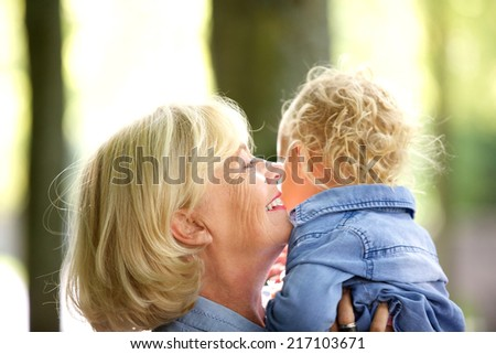 Close up portrait of a happy grandmother hugging little baby girl - stock photo