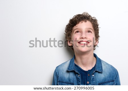 Close up portrait of a happy little boy looking up on white background  - stock photo