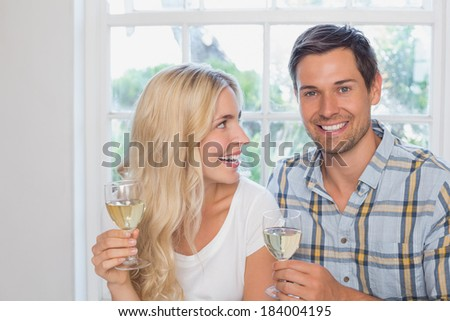 Close-up portrait of a happy loving young couple with wine glasses at home