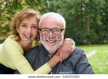 Close up portrait of a happy married couple smiling together outdoors - stock photo
