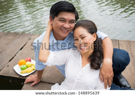 Close-up portrait of a happy mature couple resting on the riverside - stock photo