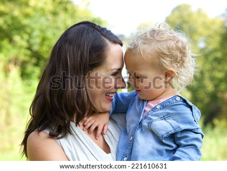 Close up portrait of a happy mother and baby smiling face to face - stock photo