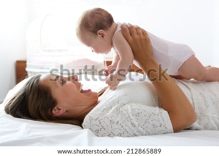 Close up portrait of a happy mother playing with cute baby in bed - stock photo