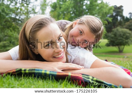 Close-up portrait of a happy mother with daughter lying at the park - stock photo