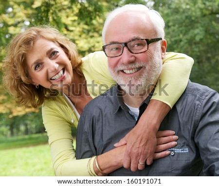 Close up portrait of a happy senior couple smiling outdoors - stock photo