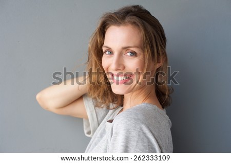 Close up portrait of a happy smiling beautiful woman posing with hand in hair against gray background - stock photo