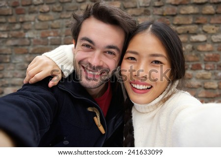 Close up portrait of a happy smiling young couple taking selfie - stock photo