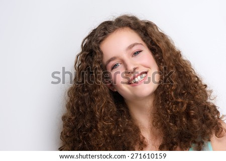 Close up portrait of a happy teenage girl smiling with curly hair - stock photo