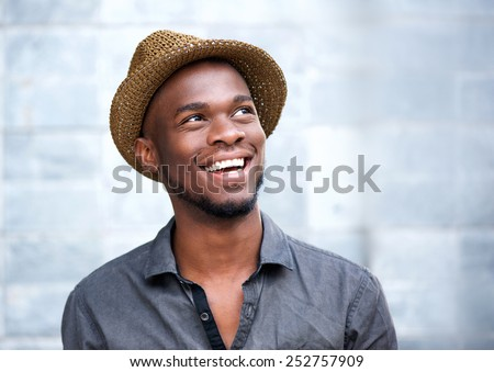 Close up portrait of a happy young african american man laughing against gray background - stock photo