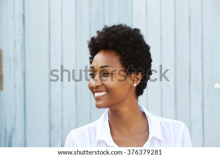 Close up portrait of a happy young african woman looking away and smiling - stock photo