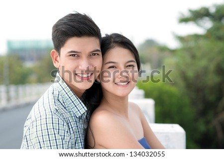 Close-up portrait of a happy young couple outdoors - stock photo