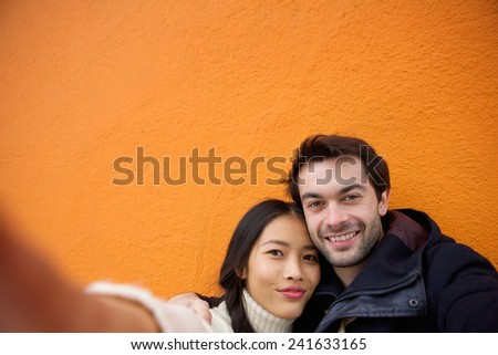 Close up portrait of a happy young couple taking selfie - stock photo