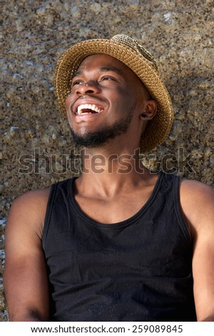 Close up portrait of a happy young man laughing with hat