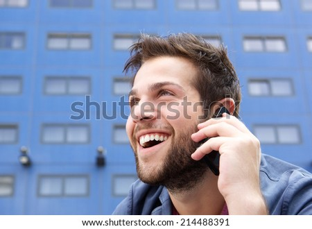 Close up portrait of a happy young man talking on mobile phone - stock photo
