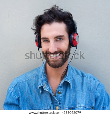 Close up portrait of a happy young man with beard listening to music with headphones - stock photo