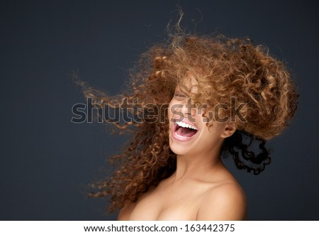 Close up portrait of a happy young woman laughing with hair blowing - stock photo