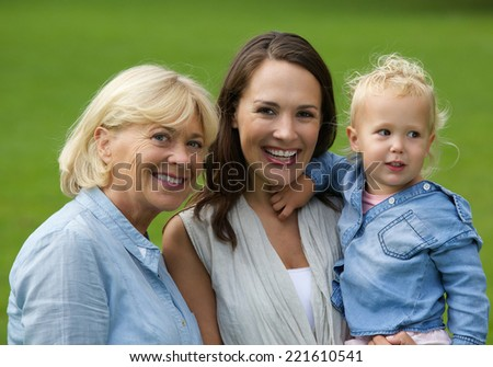 Close up portrait of a joyful family with mother, grandmother and baby daughter - stock photo