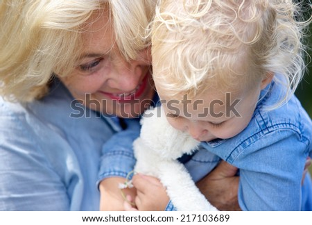 Close up portrait of a joyful grandmother holding baby girl - stock photo
