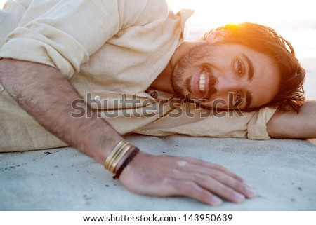 Close up portrait of a joyful young attractive man lying down and relaxing on a white sand beach with the sunset behind him with flare and warm flooding light on vacation, smiling. - stock photo